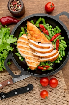 Top view grilled chicken and peas in pan with chilli peppers and tomatoes
