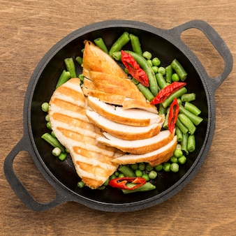 Top view grilled chicken and peas in pan with chilli peppers