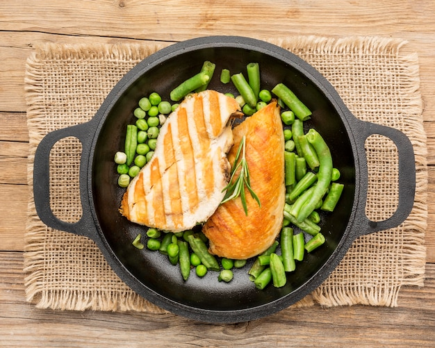 Top view grilled chicken and peas in pan with herbs