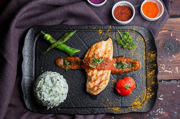 Вид сверху на гриле куриный стейк с гарниром, помидор, перец темный деревянный стол