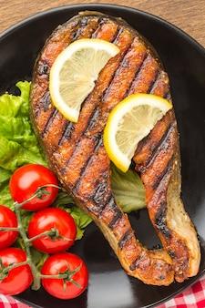 Вид сверху жареная рыба с ломтиками лимона