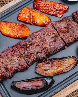 Вид сверху на гриле мясо с болгарским перцем и жареным баклажаном на подносе
