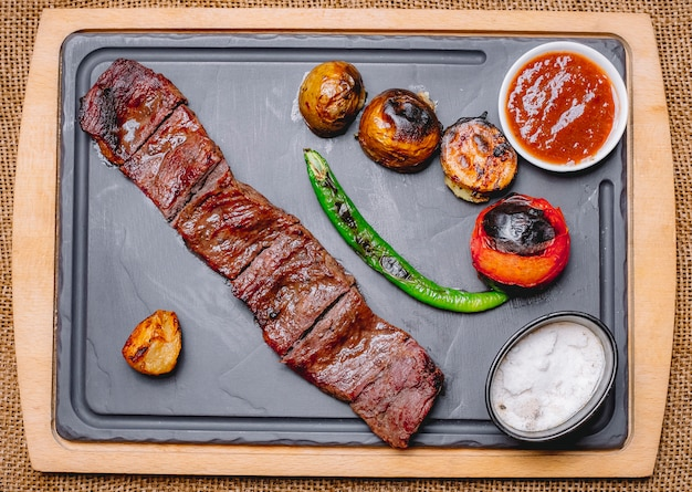 Top view grilled meat with potatoes and grilled vegetables with ketchup and mayonnaise