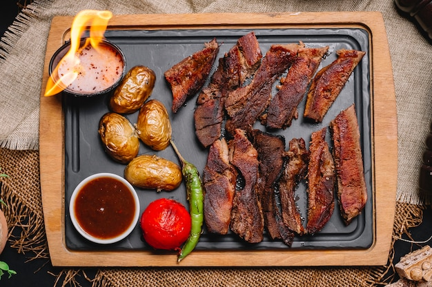 Top view grilled meat with potatoes and grilled vegetables with sauces