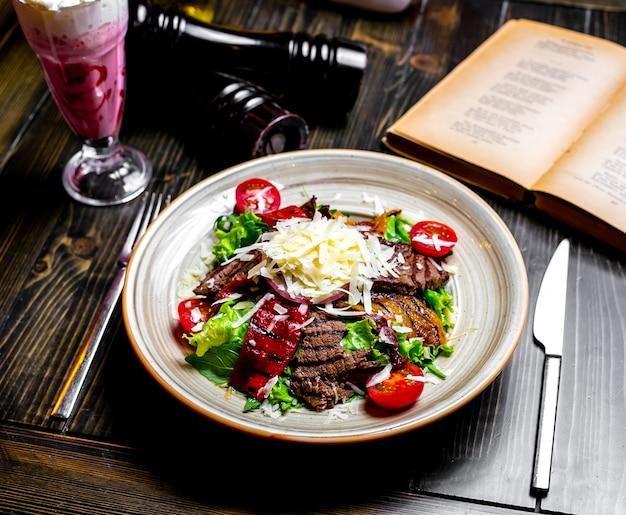 Вид сверху на гриле мясо с овощами и листьями салата с тертым сыром на тарелке