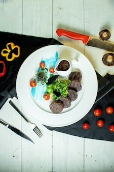Top view of grilled medallions of beef with cherry tomatoes and sauce on a plate