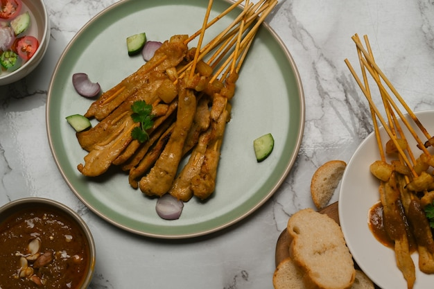 Top view of grilled pork satay (moo satay) with cucumber served with peanut sauce and grilled bread on marble desk