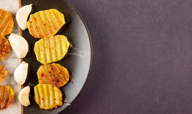 Vista dall'alto patate alla griglia e aglio a sinistra con copia spazio su sfondo grigio scuro