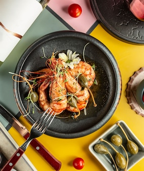 Top view of grilled prawns garnished with pickles and flowers