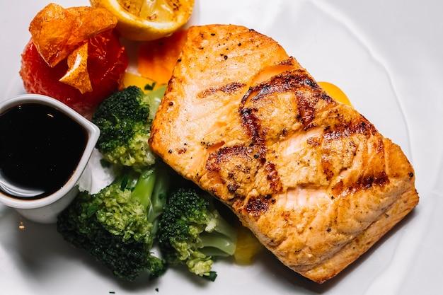 Вид сверху на гриле стейк из красной рыбы с брокколи, ломтиком лимона, помидорами и соусом наршараб