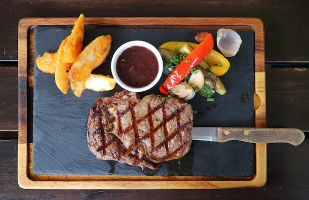 Top view of grilled ribeye steak with red wine sauce served on hot stone plate
