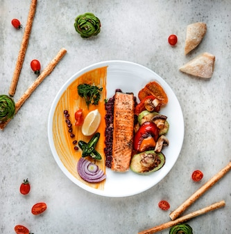 Top view of grilled salmon steak with vegetables lemon and spices on a white plate on white