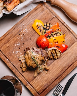 Vista dall'alto bistecca alla griglia con zucchine peperone pomodoro salsa di funghi funghi sale e pepe nero su una tavola
