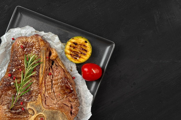 Top view of grilled t-bone steak with spices on black table