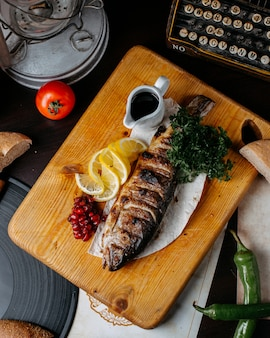 Top view of grilled trout with lemon and pomegranate seeds on a wooden cutting board