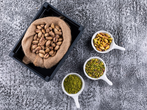 Top view ground, milled, crushed or granulated pistachios in sack on gray texture background horizontal