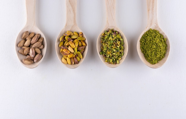 Top view ground, milled, crushed or granulated pistachios in wooden spoons on white