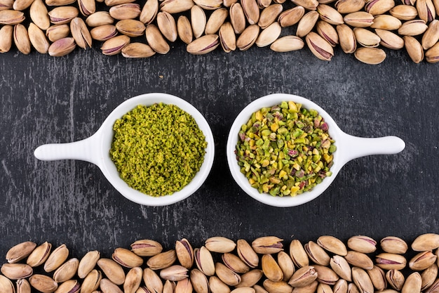 Top view ground, milled, crushed pistachios in a bowl on gray texture