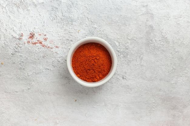 Vista dall'alto pepe macinato arancione colorato su scrivania bianca pepe ingrediente prodotto cibo spezia calda