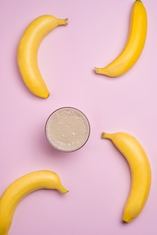 Top view. group of bananas and banana smoothie on pink background.