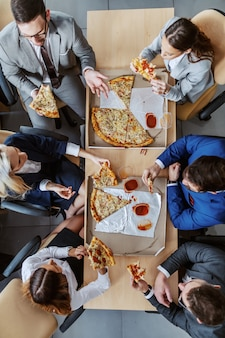 Top view of group of business people sitting at table, eating pizza for lunch and chatting.