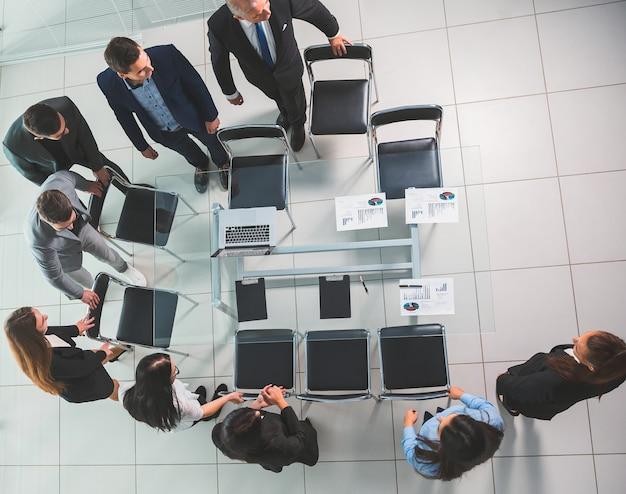 Вид сверху. сотрудники группы идут в конференц-зал. бизнес-концепция