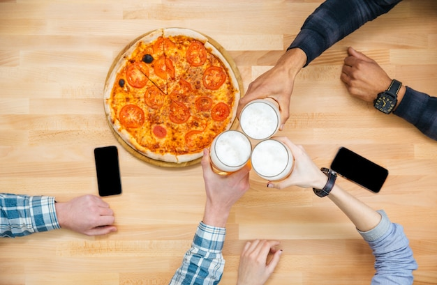 Top view of group of friends eating pizza and drinking beer