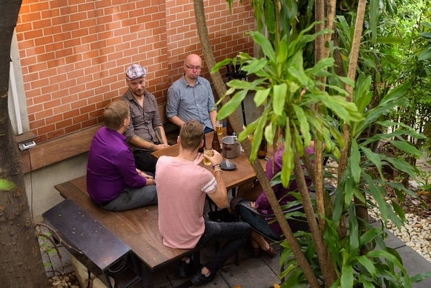Top view of group of men outdoors sitting and drinking beer