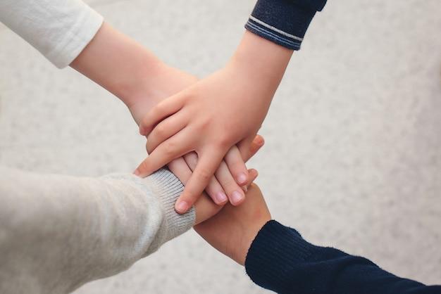 屋外で手を積み重ねる子供たちのトップビューグループ。友情、団結、チームワークの概念。手で積み重ねられた学校の友達のグループ。学校に戻る。