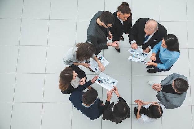 평면도. 원 안에 서있는 회사 직원의 그룹입니다. 공간의 사본이있는 사진