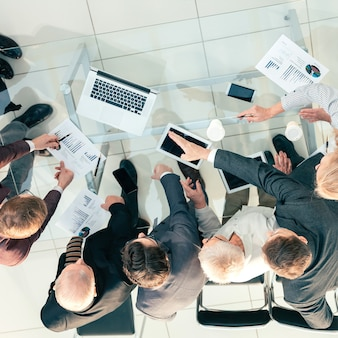 上面図。財務統計について話し合う従業員のグループ