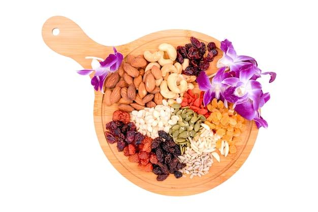Группа вид сверху цельного зерна и сухофруктов с красивым орком спряталась на деревянной тарелке, изолированной на белом фоне.