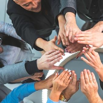 上面図。輪になって立っている若いビジネスマンのグループ。チームワークの概念