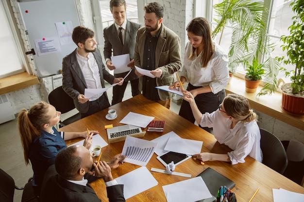 Вид сверху. группа молодых бизнес-профессионалов на встрече. разнообразная группа сотрудников обсуждает новые решения, планы, результаты, стратегию. творчество, рабочее место, бизнес, финансы, работа в команде.
