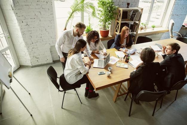 上面図。会議をしている若いビジネス専門家のグループ。同僚の多様なグループが、新しい決定、計画、結果、戦略について話し合います。創造性、職場、ビジネス、財務、チームワーク。