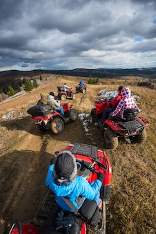 Top view of a group of people riding an atv on a mountain road under a sky with clouds in sunny autumn day
