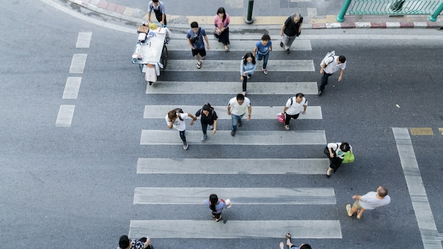Top view of group people walk on the crosswalk with white sign pedestrian