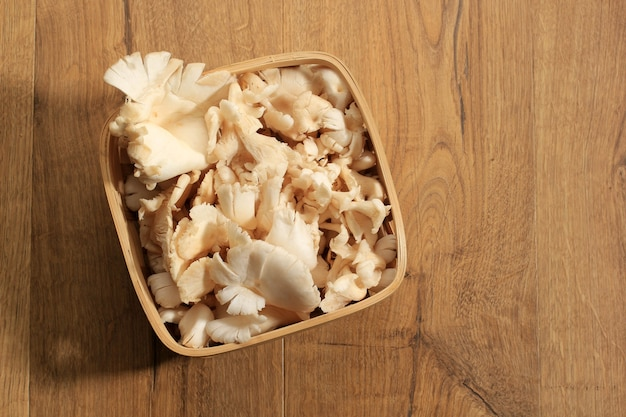 Top view a group of white oyster mushroom on wicker basket on brown wooden table ready to cook in the kitchen