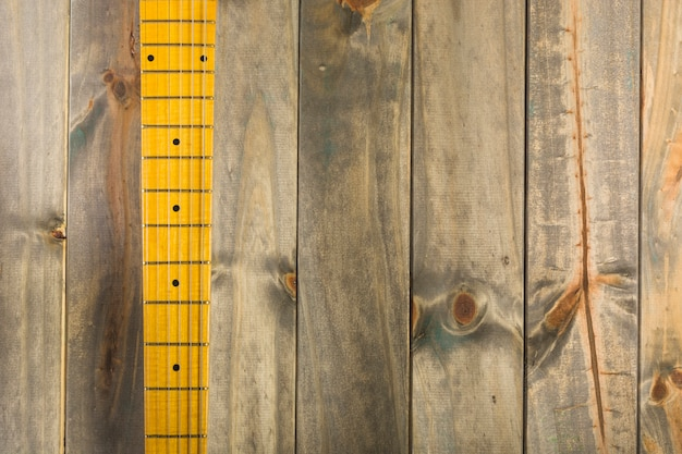 Top view of guitar strings and fret board on wooden background