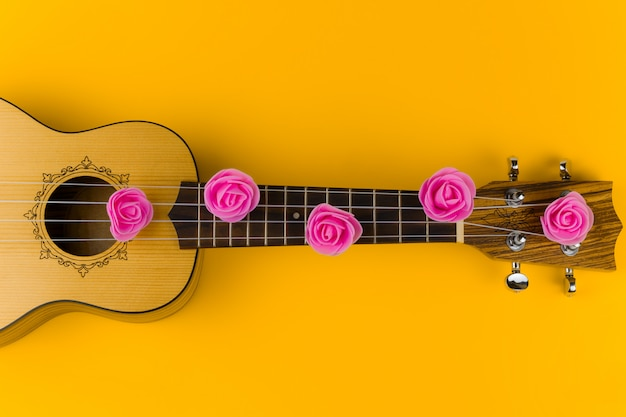 Top view of a guitar with rose flowers on the strings lies on vibrant yellow