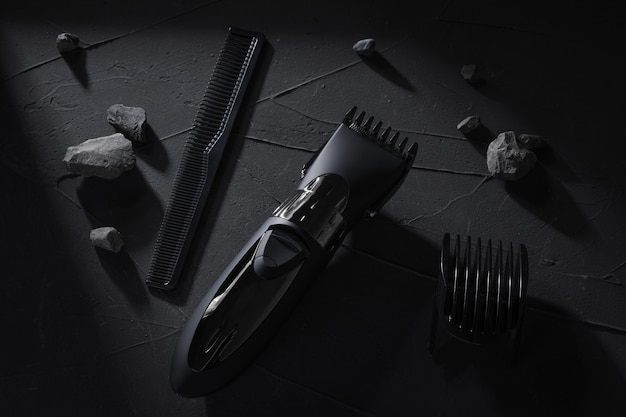 Top view. hair and head trimmer on dark concrete table with hard shadows