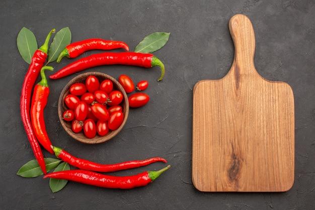 Vista dall'alto semicerchio di peperoncini rossi e foglie di alloro e una ciotola di pomodorini e un tagliere sulla tavola nera