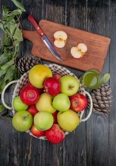 Top view of half cut apple and knife on cutting board with apple juice basket of apples pinecone and leaves on wooden table