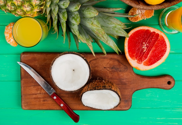 Top view of half cut coconut and knife on cutting board with grapefruit pineapple tangerine and orange juice on green background