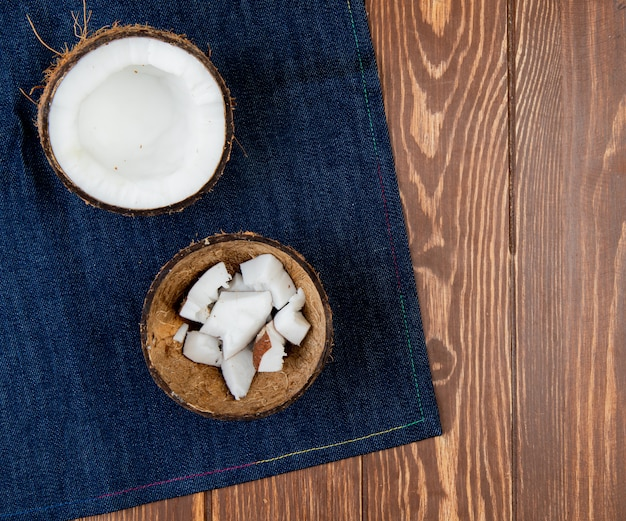 Top view of half cut coconut with coconut slices in shell on jeans cloth and wooden background with copy space