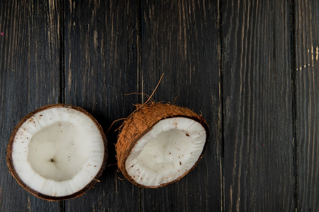 Top view of half cut coconut on wooden background with copy space