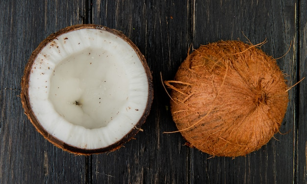 Top view of half cut coconut on wooden background