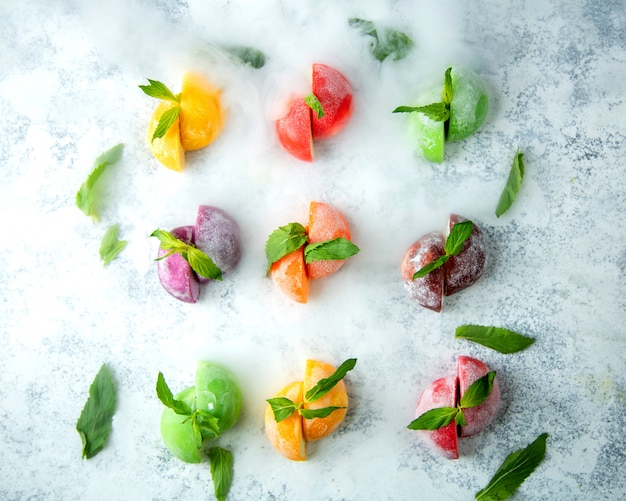 Top view of half cut frozen fruits garnished with mint leaves