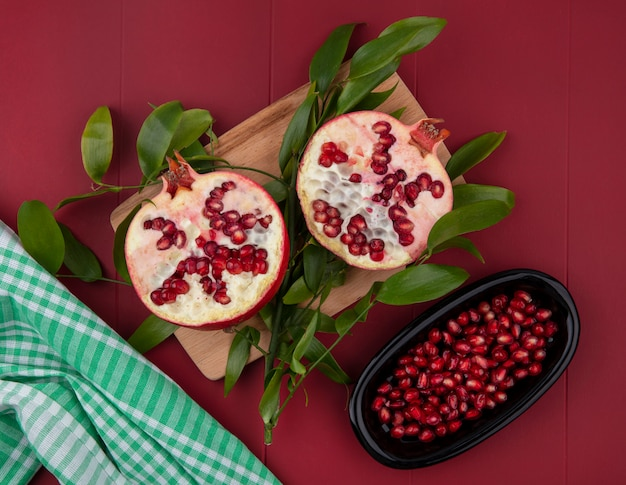 Top view of half cut pomegranate and leaves on cutting board with pomegranate berries in plate and plaid cloth on red surface