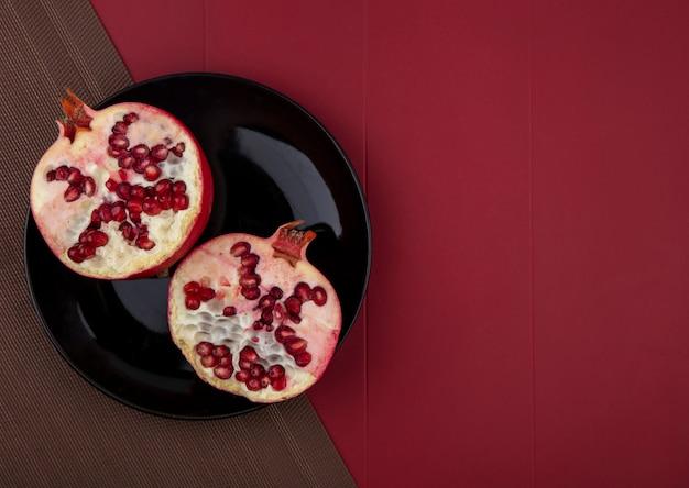 Vista dall'alto di mezzo taglio melograno nel piatto sul panno sulla superficie rossa